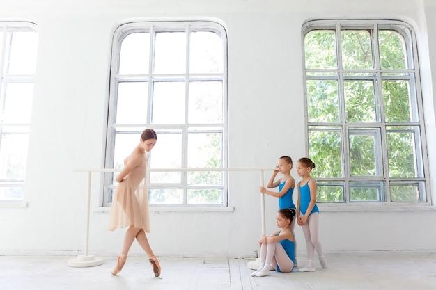 Tres pequeñas bailarinas con profesora de ballet personal en el estudio de danza. bailarina de ballet clásico como profesor posando sobre una pierna en la barra de ballet en un estudio blanco