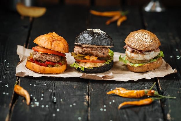 Tres pequeñas hamburguesas en la mesa de madera oscura.