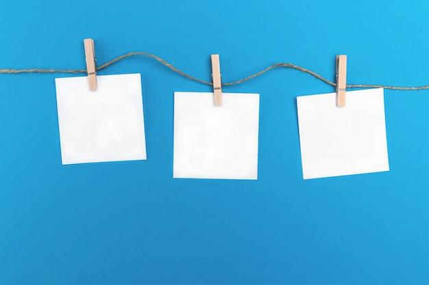 Tres pequeñas hojas de papel vacías se sujetan con pinzas de madera en una cuerda