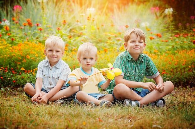 Tres pequeños hermanos que se sientan en hierba en día de verano soleado.