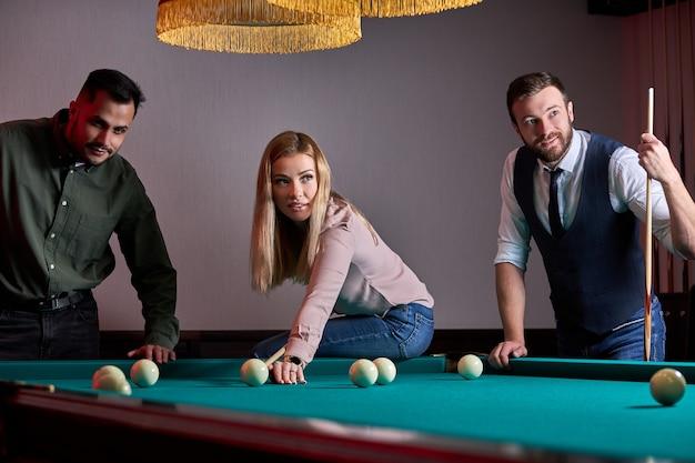 Tres personas amables mirando pelotas en la mesa de billar, jugando juntos un juego deportivo