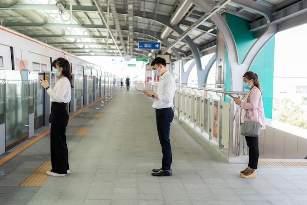 Tres personas asiáticas que usan una máscara a una distancia de pie de 1 metro de otras personas mantienen la distancia protegidas de los virus covid-19 y el distanciamiento social de las personas