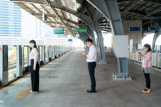 Tres personas asiáticas que usan una máscara de pie a una distancia de 1 metro de otras personas mantienen la distancia protegida contra los virus covid-19 y las personas distanciamiento social por riesgo de infección