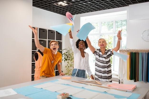 Tres personas creativas de pie en un estudio mientras celebran la creación de una nueva colección.