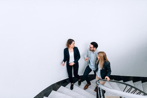 Tres personas hablando mientras caminan por las escaleras en el edificio de oficinas.