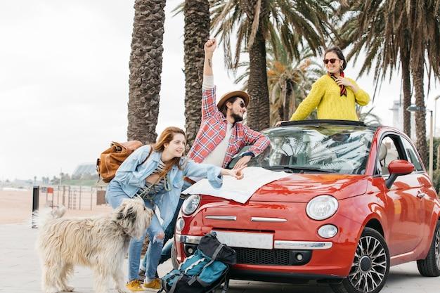 Tres personas y un perro de pie cerca de un coche con un mapa de carreteras