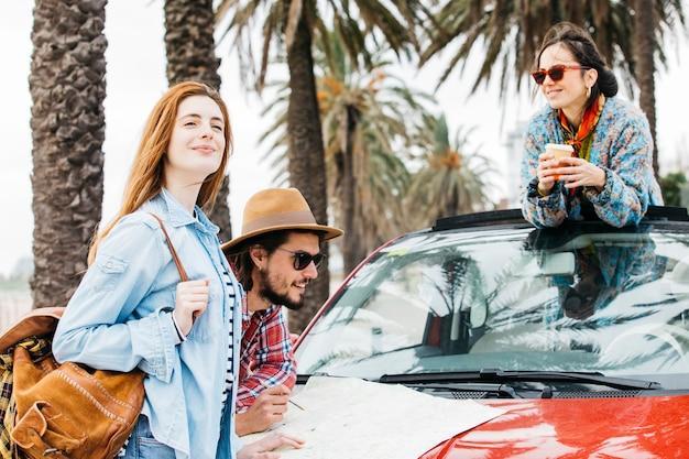 Tres personas de pie cerca del coche con el mapa de carreteras