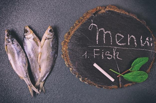 Tres pescados secos sobre una superficie negra
