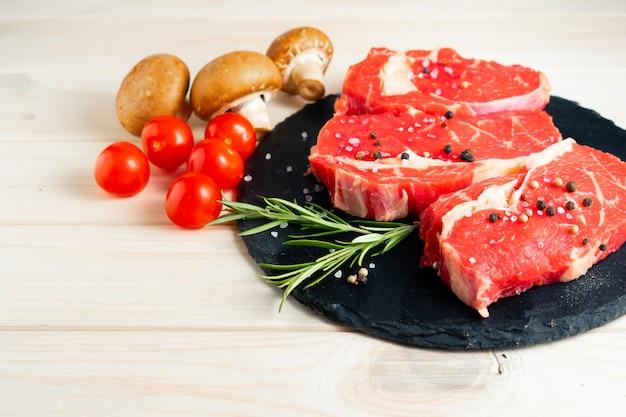 Tres piezas de jugosa carne cruda en una tabla para cortar piedra en una mesa de madera blanca