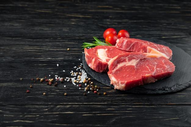 Tres piezas de jugosa carne cruda en una tabla para cortar piedra