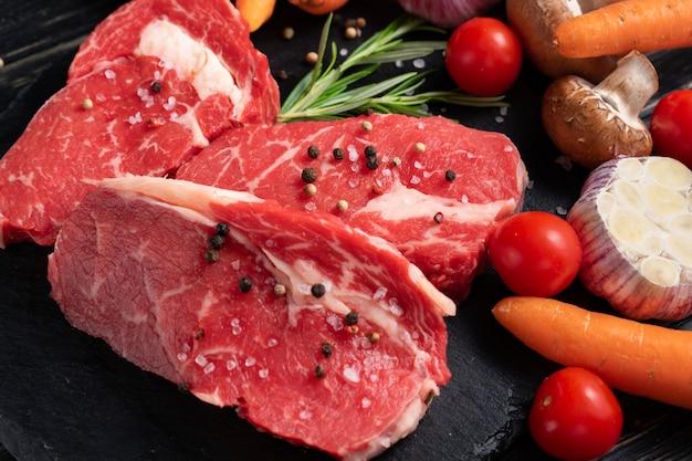 Tres piezas de jugosa carne cruda con verduras en una tabla para cortar piedra en una mesa de madera negra