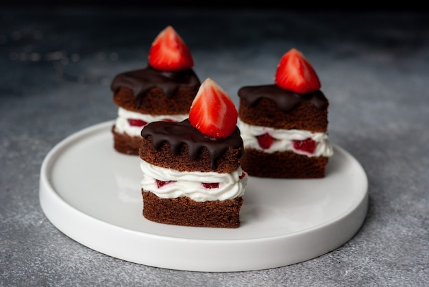 Tres piezas de pastel de chocolate con capas de fresa con crema blanca sobre fondo gris oscuro