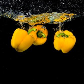 Tres pimientos amarillos flotando bajo el agua