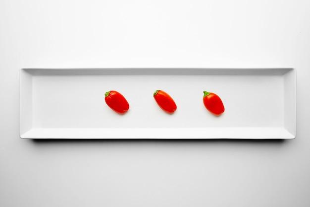 Tres pimientos rojos aislados en el centro de la placa de cerámica rectangular sobre fondo blanco.