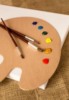 Tres pinceles sobre palet de madera con manchas de pintura al óleo