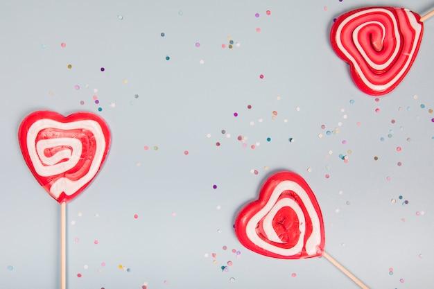 Tres piruletas rojas de la forma del corazón en fondo gris con confeti colorido