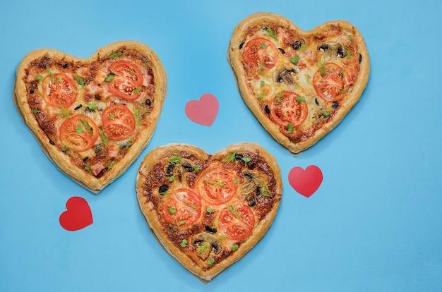 Tres pizzas en forma de corazón sobre una mesa azul con corazones rojos. pide pizza para una cena romántica el día de san valentín. amor.-