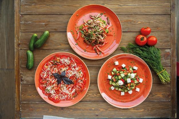 Tres platos de ensaladas de verduras en platos rojos.