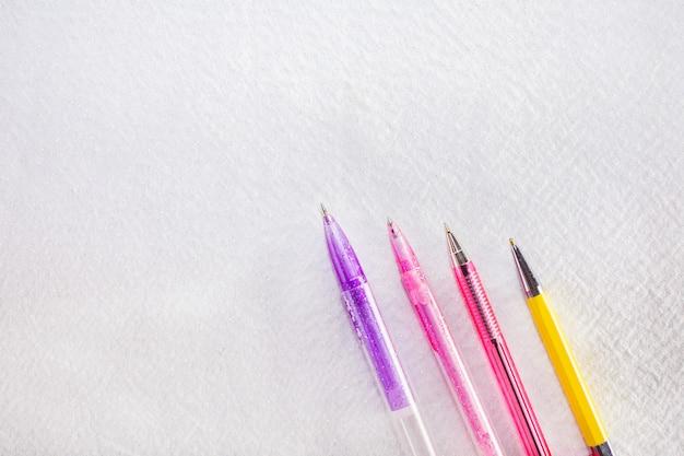 Tres plumas aisladas en blanco. bolígrafos de color rosa, violeta y amarillo.