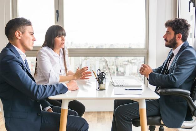 Tres profesionales de negocios discutiendo en la oficina.
