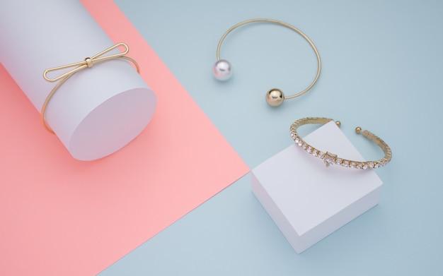 Tres pulseras doradas sobre fondo de papel rosa, azul y blanco