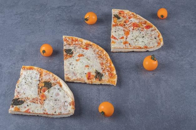 Tres rebanadas de pizza fresca sobre fondo gris.