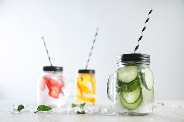 Tres refrescos fríos de fresa, naranja, lima, menta, hielo y agua con gas en frascos rústicos con pajitas en el interior