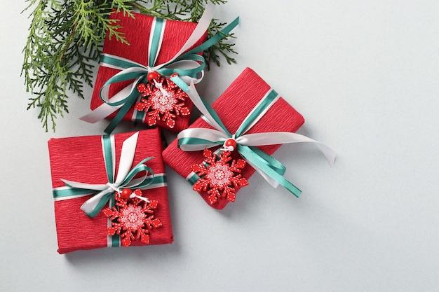 Tres regalos de navidad en papel rojo con copos de nieve y cintas sobre superficie clara
