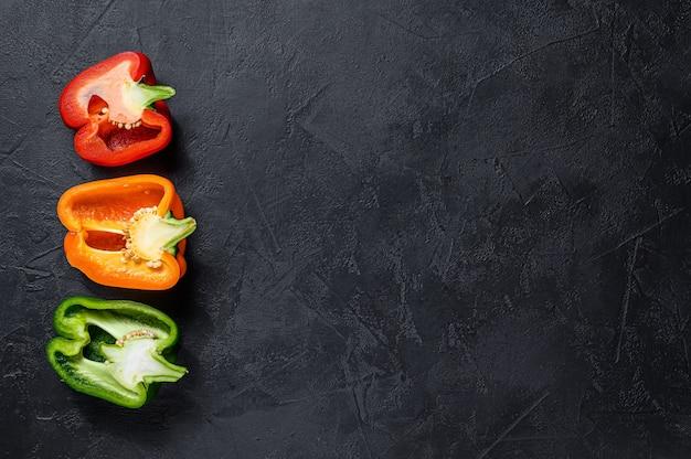 Tres rodajas de pimiento naranja, verde y rojo. fondo negro. vista superior. espacio para texto