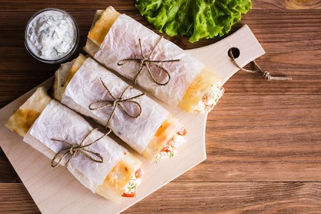 Tres rollos de pita con queso feta, pollo y tomate en una tabla de cortar. vista superior