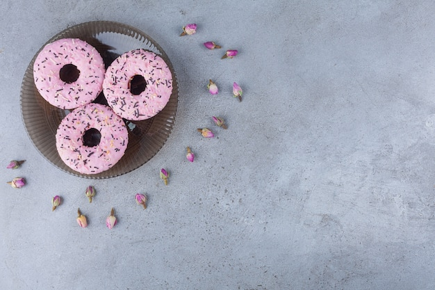 Tres rosquillas dulces rosas con rosas en ciernes en placa de vidrio.