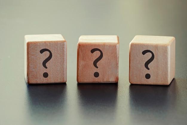 Tres signos de interrogación en una fila de bloques de madera.