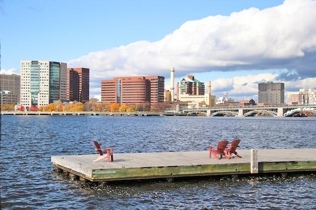 Tres sillas rojas en el muelle. paisaje urbano y puente sobre el río.