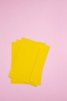 Tres sobres amarillos sobre fondo rosa