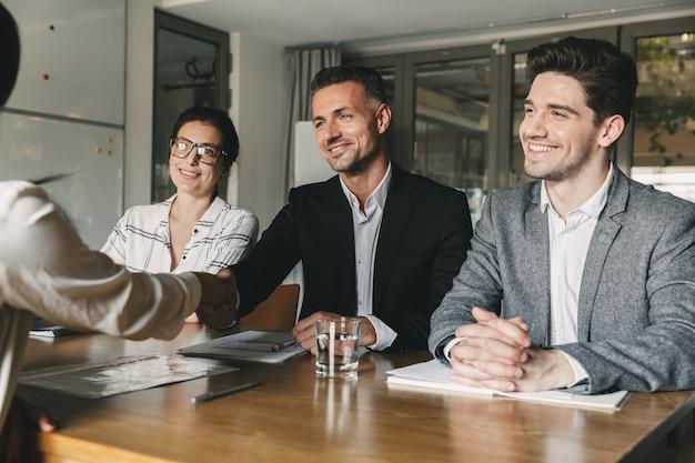 Tres socios comerciales en la oficina apretón de manos con la mujer, como resultado de una colaboración exitosa o iniciando una asociación después de negociaciones efectivas