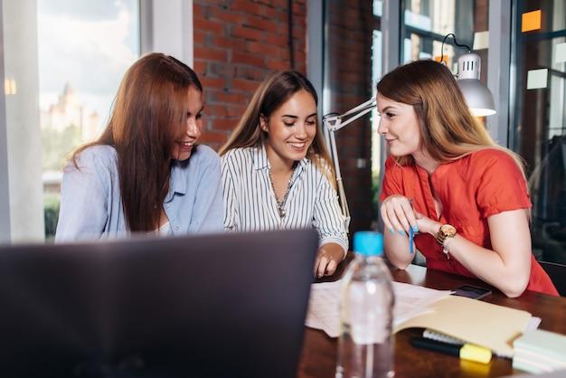Tres sonrientes estudiantes universitarios que trabajan juntos en el proyecto en el aula
