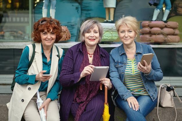 Tres sonrientes mujeres rusas maduras con dispositivos móviles en sus manos están sentados en la calle de la ciudad europea frente a la ventana de la tienda de comestibles.