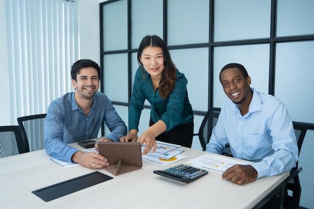 Tres sonrientes profesionales corrieron mezcla discutiendo nuevo proyecto en la mesa de conferencias.