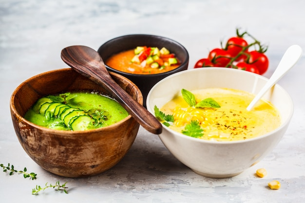 Tres sopas de crema de verduras diferentes en tazones sobre sopas de maíz gris, pepino y gazpacho,