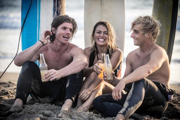 Tres surfistas relajándose en la playa después del deporte