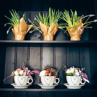 Tres tazas blancas con flores en el estante.