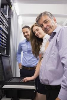 Tres técnicos felices que controlan los servidores con la computadora portátil