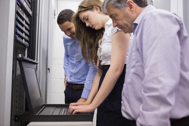 Tres técnicos que miran la computadora portátil