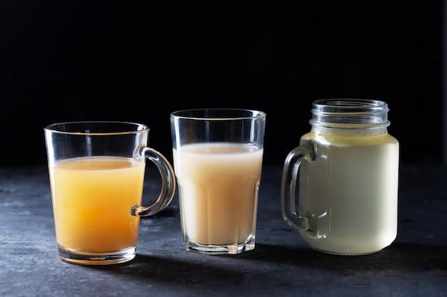 Tres tipos de caldo de hueso de res casero en vasos en un espacio negro