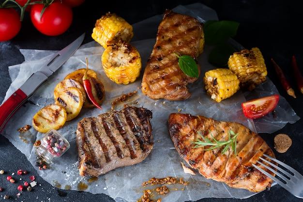 Tres tipos de carnes a la brasa con verduras y especias sobre papel.
