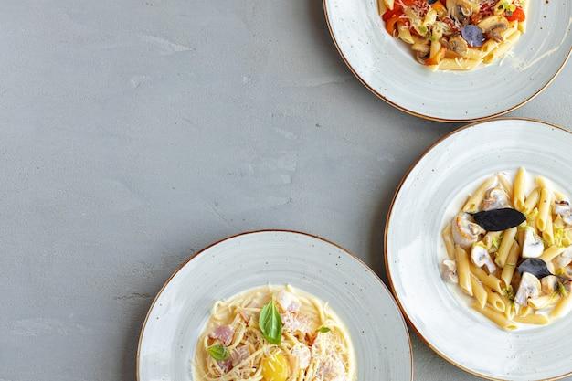 Tres tipos de pasta servida en la vista superior de la mesa gris