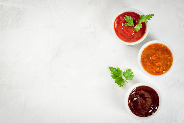 Tres tipos de salsa de tomate rojo sobre una mesa de piedra blanca: salsa de tomate clásica tradicional, salsa de barbacoa, salsa china agridulce. vista superior copia espacio