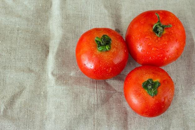 Tres tomates maduros rojos con gotas de agua sobre el fondo gris
