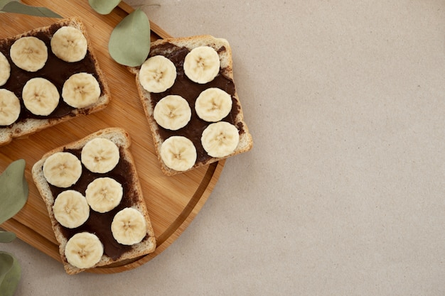 Tres tostadas de pan de plátano blanco untadas con chocolate.