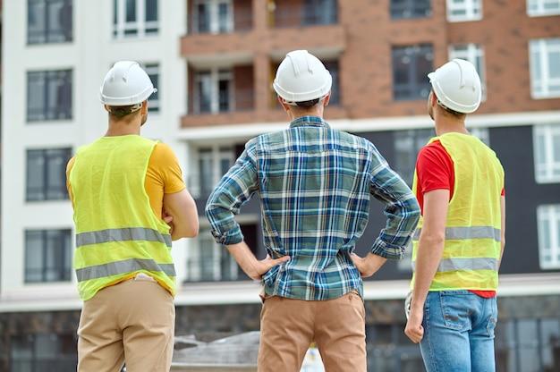 Tres trabajadores con cascos de pie ante un nuevo edificio